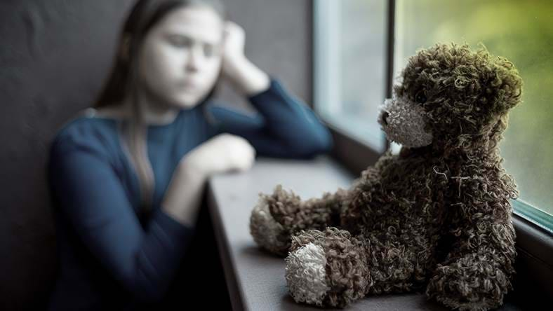 Girl leaning against window with bear