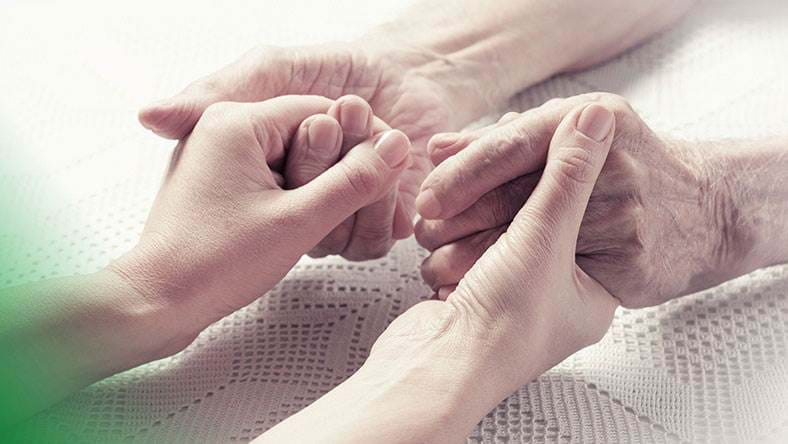 Elderly person holding hands