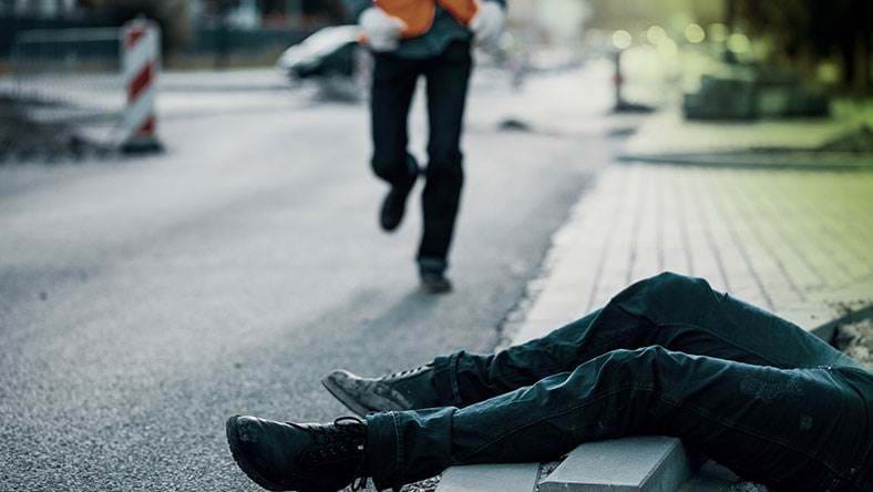 Man lay injured at road side with work man running over