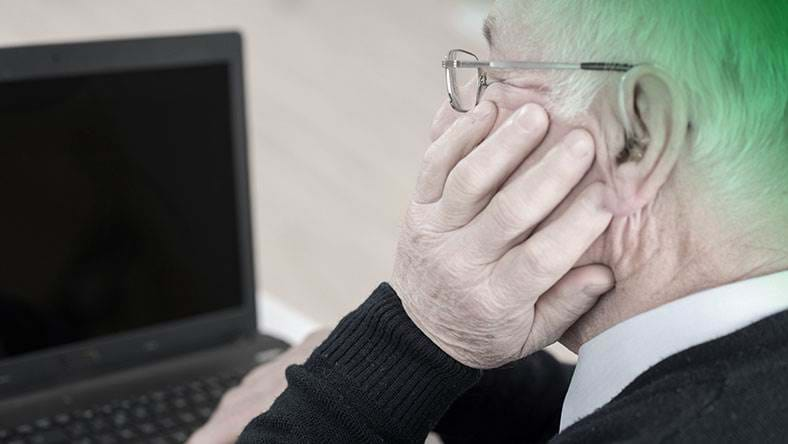 elderly man with hearing aid looking at laptop