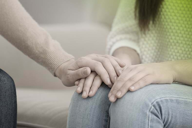 Woman sat on sofa being comforted holding hand