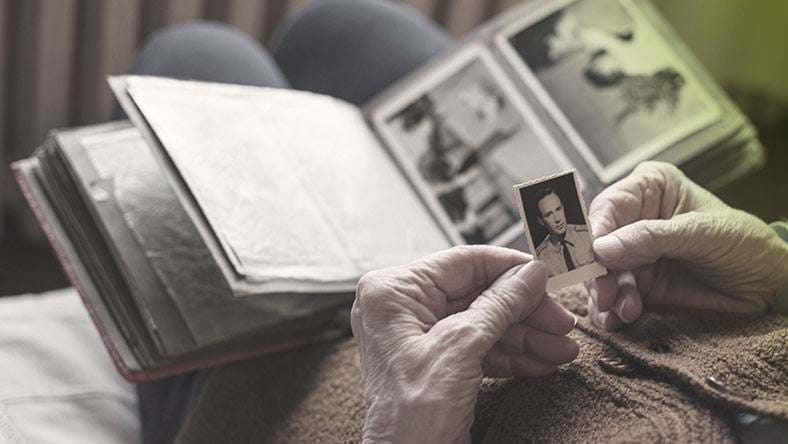 elderly person reminiscing over old photos