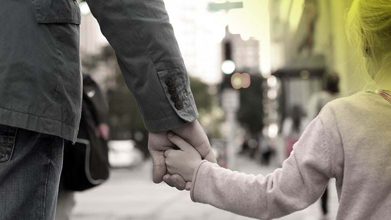 young girl holding mans hand