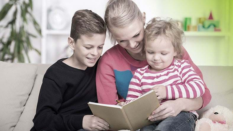 father and children sat together reading