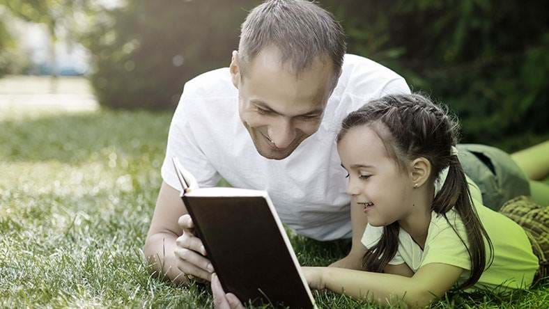 father and daughter lay in field  happy reading
