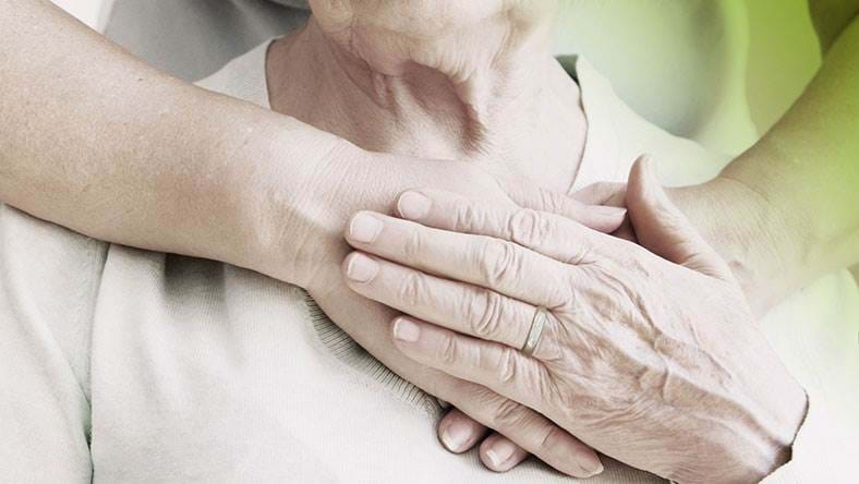 elderly woman being comforted by younger woman hand on chest