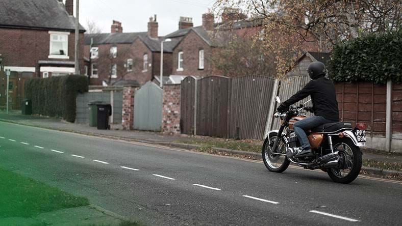 motorcyclist riding down road with leather jacket and helmet