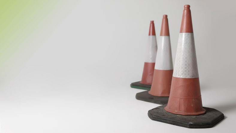 traffic cones lined up on white background