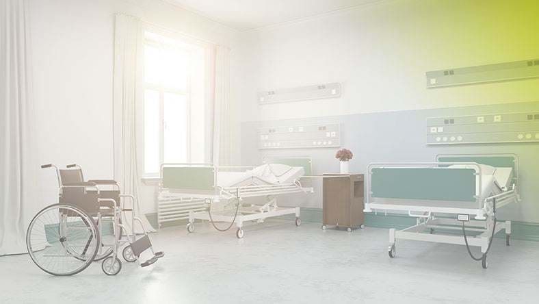empty hospital bed and wheelchair in hospital room