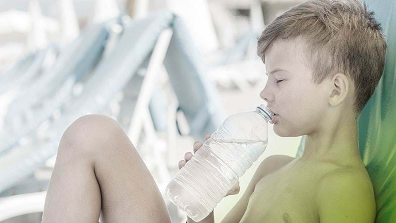 young boy on sun lounger on holiday drinking bottle of water