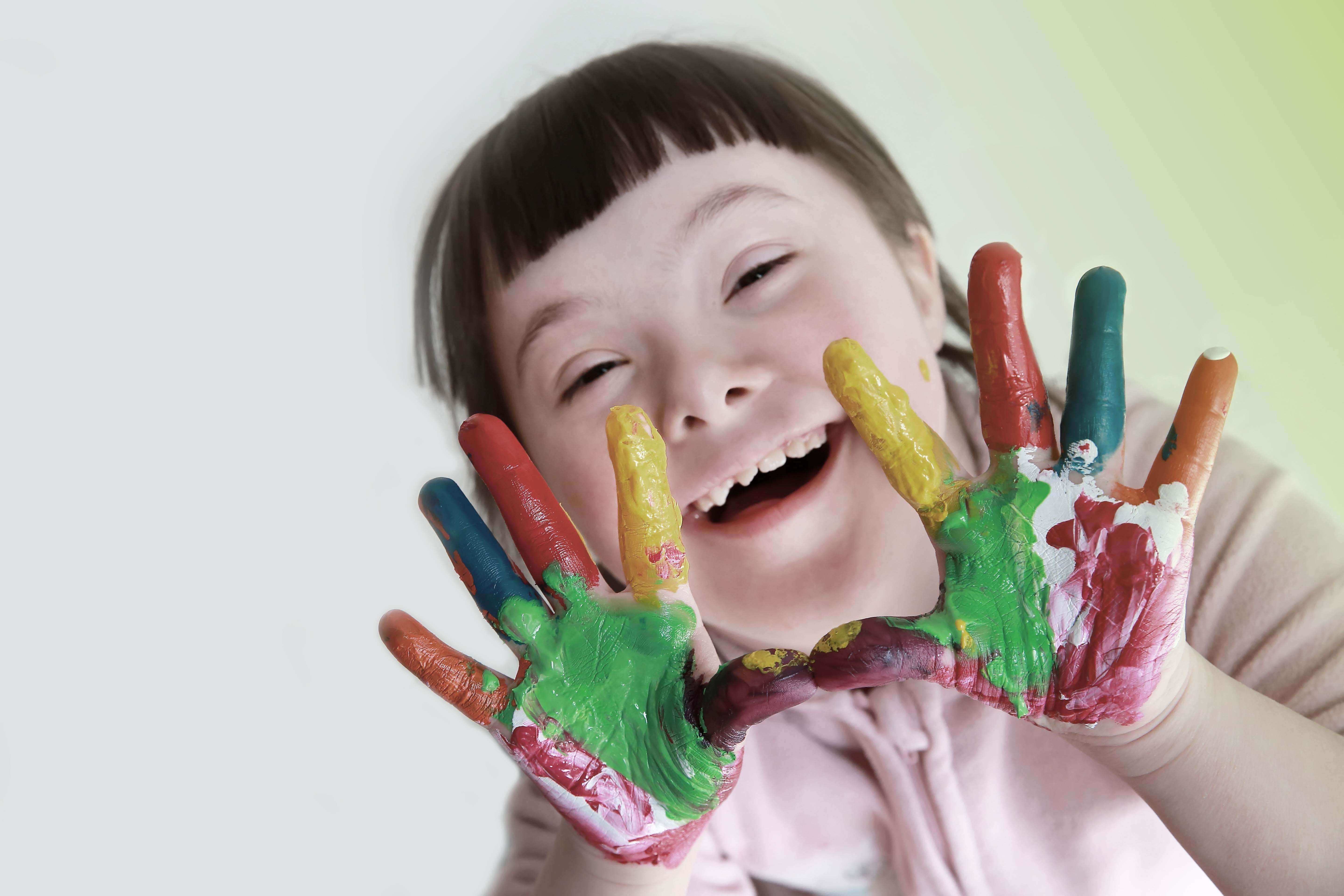 happy child with paint on hands smiling