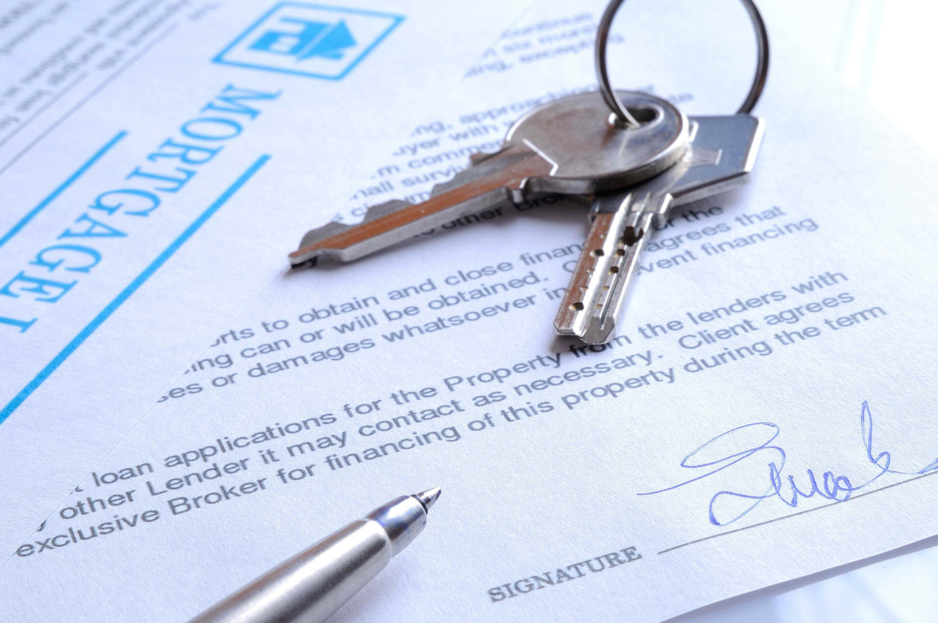 A pen with signed Mortgage papers and keys