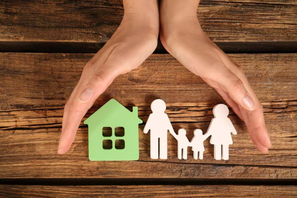 Wood cutout of a house and family, with human hands protecting from the top