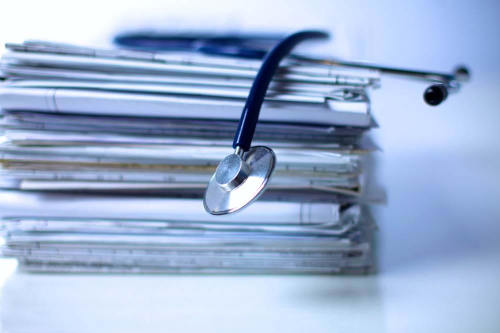 Pile of medical notes and stethoscope