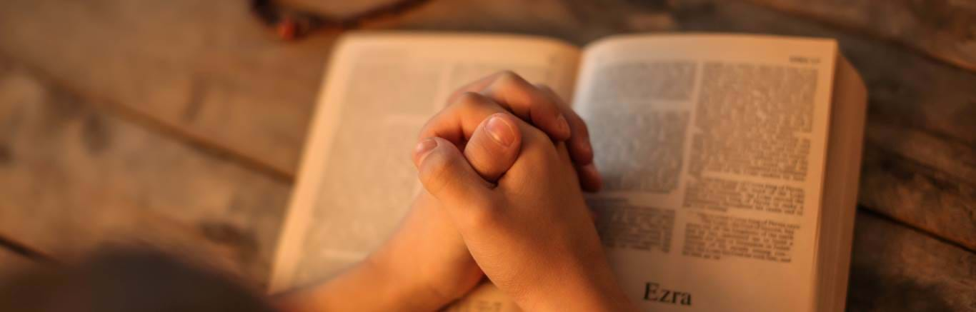 Young person with hands in prayer on a bible