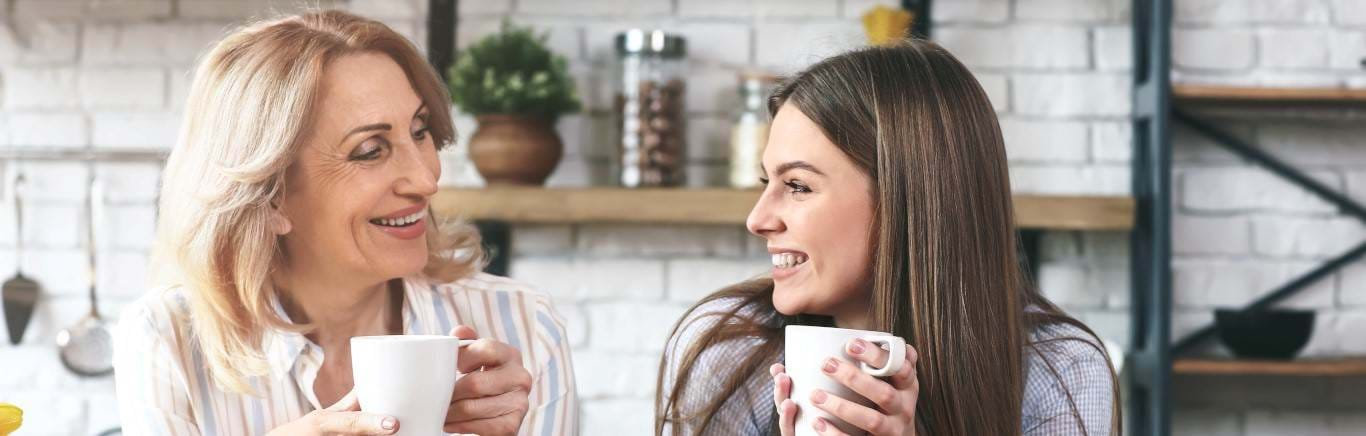 Young woman having cup of tea with mum